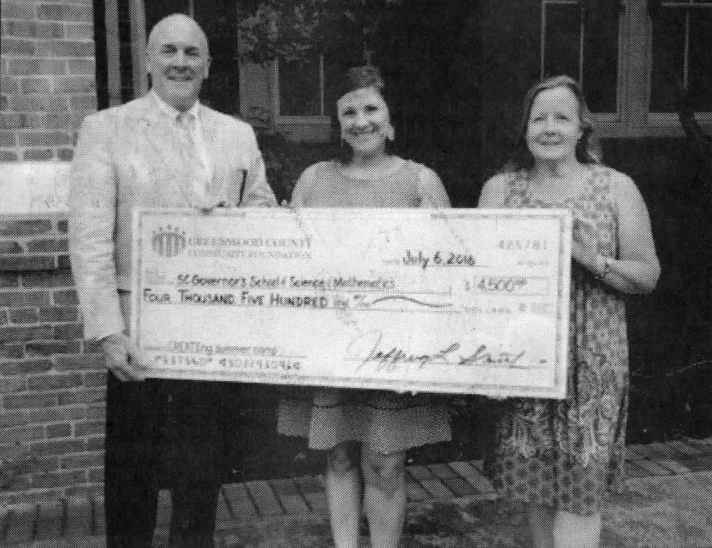 Mary Kathryne Elliot, center, annual fund and grants manager for the SC Governor's School of Science and Mathematics, accepts a check from the Greenwood County Community Foundation in support of CREATEng Engineering Camp.